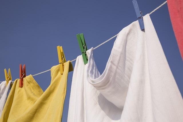 カラフルな洗濯バサミと洗濯紐で陰干ししてある洗濯物