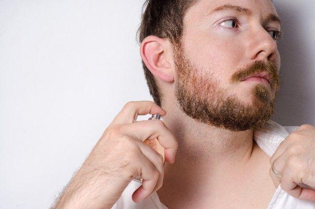首筋に香水をスプレーする髭の外国人男性