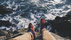 海岸の岩の上でくつろぐロールアップの外人男性の脚
