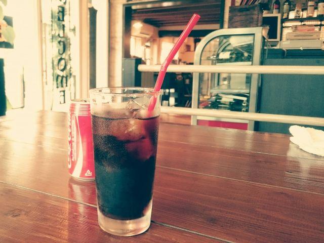 氷入りのグラスに入ったコーラと空き缶