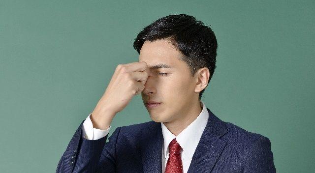 眼精疲労で目を押さえる男性ビジネスマン