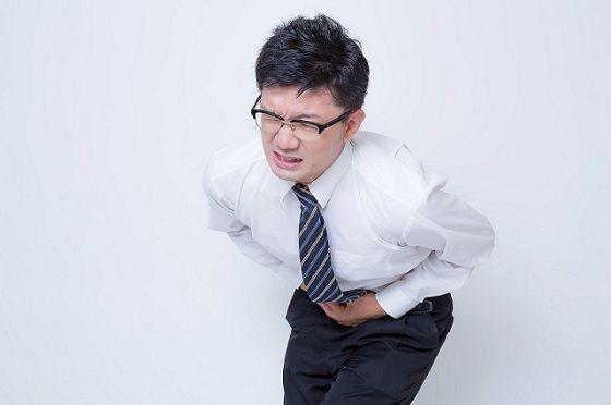腹痛でお腹を押さえる男性
