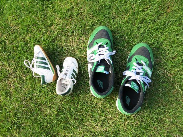 芝生に並んだ大人用ジョギングシューズと子供用ジョギングシューズ