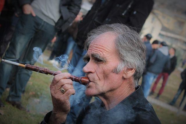 タバコを吸う白髪の男性