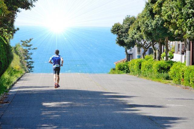 光っている海に向かってアスファルトの上を走る男性