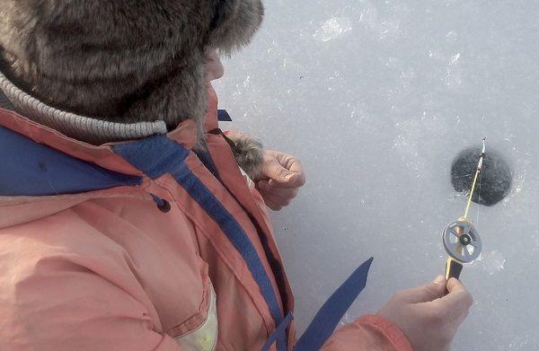 毛皮コートを着て氷上に穴を開けて一人でワカサギ釣りをする男性