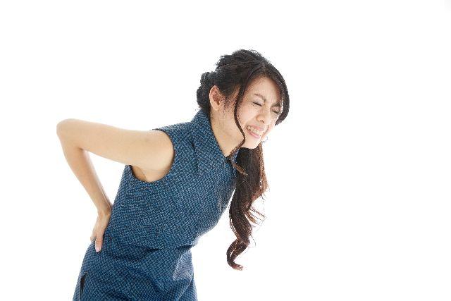 腰が痛くて中腰になっている女性