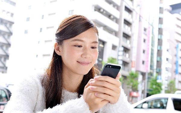 街中でスマートフォン携帯電話を閲覧する留学生少女