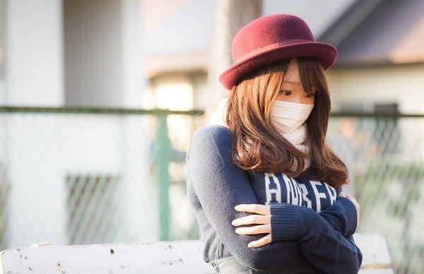厚着姿で寒がる帽子の若い女性