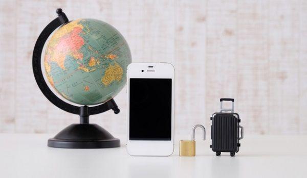 地球儀と携帯電話(iPhone)と南京錠とコロ付き旅行カバン