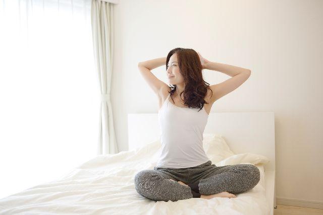 タンクトップで寝起きの健康女性
