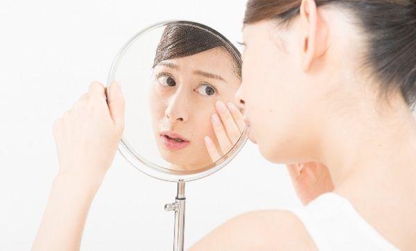 鏡を覗き込んで肌の調子を心配する女性