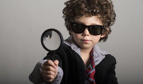 虫眼鏡を覗き込むサングラスの子供