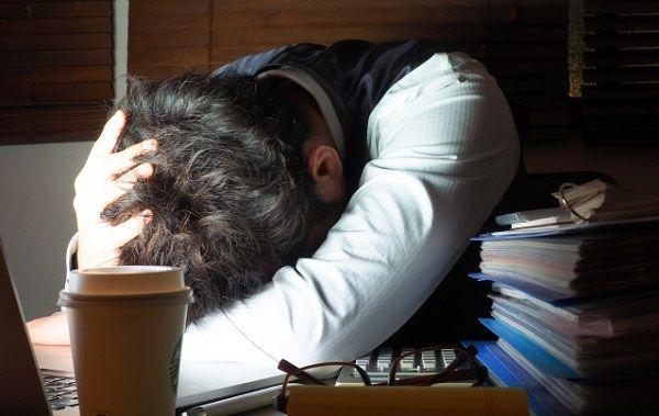 疲れで机にうつ伏せになっている男性ビジネスマン