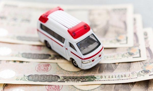 治療費をイメージした救急車とお金