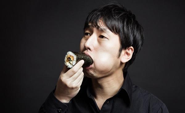 巻き寿司を口いっぱいに頬張る男性