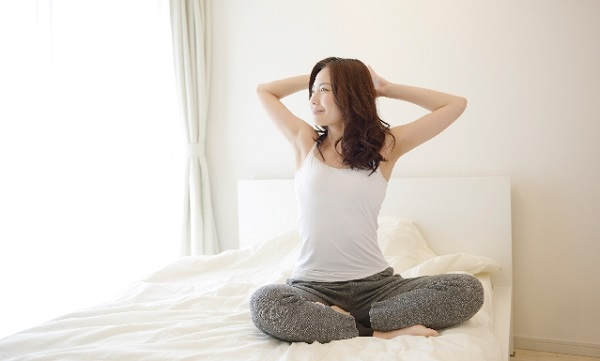 ベッドの上で背伸びをする薄着の若い女性