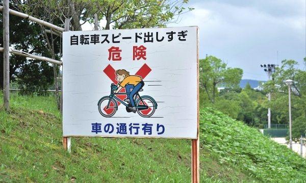 「自転車スピード出しすぎ危険」と書かれた看板