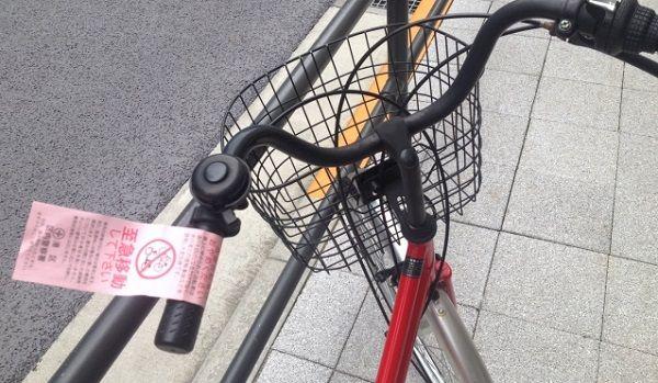 「至急移動してください」という張り紙がされた自転車のハンドル