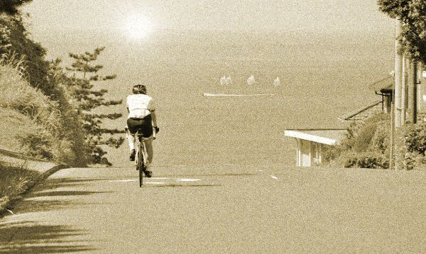海沿いの道路を走る自転車(古ぼけた写真)