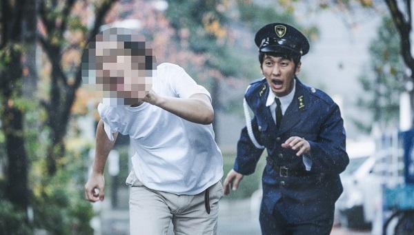路上で怪しい男を追いかける警察官