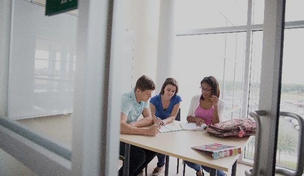 教室で団欒する外国人生徒を引きで見る視線