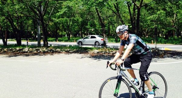 公園で自転車を楽しむサングラスの外国人男性