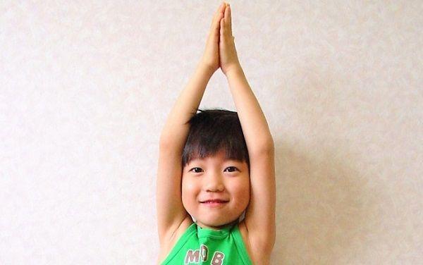 手を上に伸ばして伸びする子供