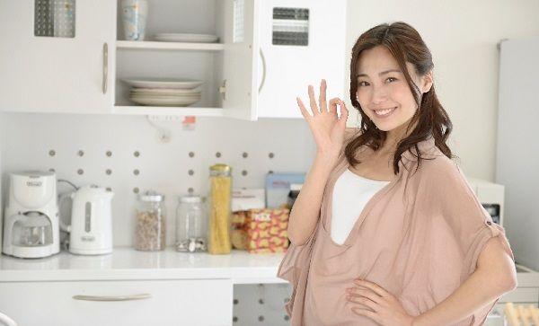 キッチンでオッケーマークを出す若い女性