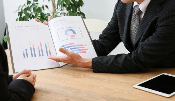 資料を見せながら説明をする営業マン