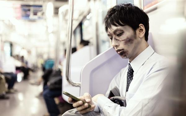 電車に座ってスマホをイジるゾンビのサラリーマン男性