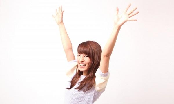 両手を上げて喜ぶ若い女性