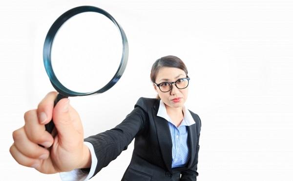 虫眼鏡で何かを発見するビジネス女性