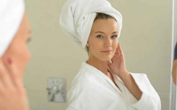 入浴後に洗面所の鏡を見る白人女性