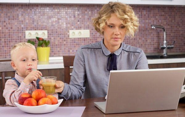 パソコンをしながら子供にグリーンスムージーを与える母親