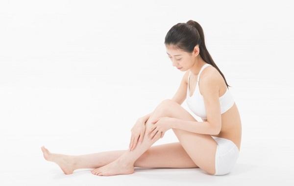 脚のマッサージをする美脚女性